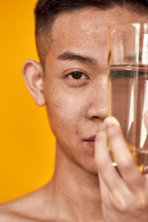 Close up portrait of young asian man looking at camera, holding a glass of water near his face isolated over yellow background. Health care, wellness concept Banque d'images