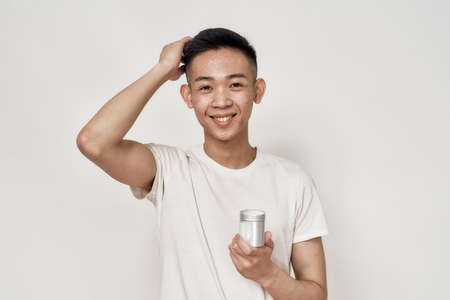 Portrait of young asian man with problematic skin and hyperpigmentation on his face smiling at camera, holding cream jar isolated over white background. Beauty, skincare, treatment concept