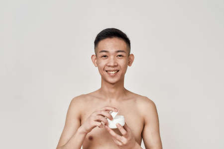 Portrait of young asian man with problematic skin and hyperpigmentation on his face smiling at camera, opening cream jar isolated over white background. Beauty, skincare, treatment concept Stock Photo