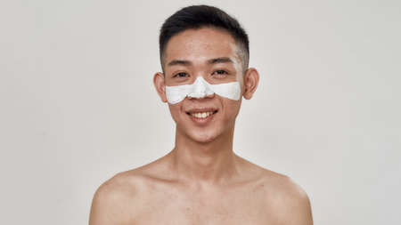 Portrait of shirtless young asian man with problematic skin and hyperpigmentation applied mask on his face, smiling at camera isolated over white background. Beauty, skincare routine Banque d'images