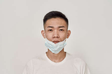 Portrait of young asian man with medical mask on his chin looking at camera isolated over white background. Health care, prevention, safety concept