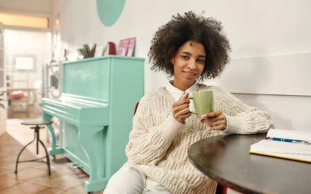 A pretty dark-skinned young woman holding a cup of coffee wearing fashionable clothes smiling and looking into a camera sitting on a chair