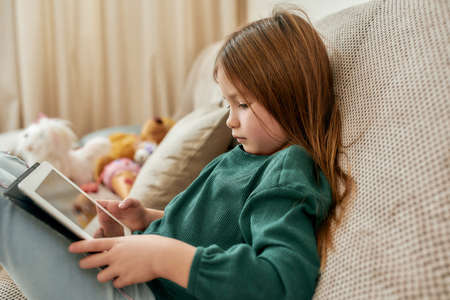 A small cute girl fully immersed into a videogame on her tablet while sitting on a sofa