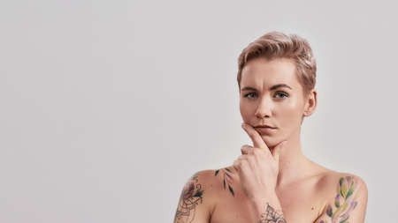 Portrait of half naked tattooed woman with short hair looking thoughtfully at camera, touching chin isolated over light background