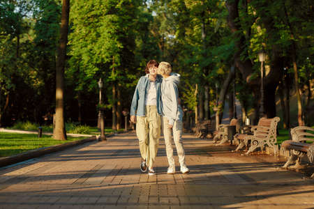 Full length shot of happy lesbian couple having a date in the city park. Two girls spending time together, kissing while walking outdoors 免版税图像