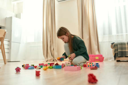 A little girl holding a couple of toy bricks while playing in a middle of a bright room 免版税图像 - 157409111
