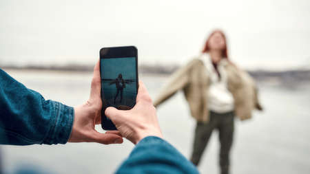 Close up of hands of young guy holding smartphone while taking photo of his girlfriend outdoors 免版税图像 - 157409295