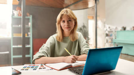A cute long blond hair woman working at a table making notes in her flipbook while looking into a camera 免版税图像 - 157409297