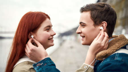 Close up of couple of teenagers going to listen to music using the same pair of earphones, looking at each other with love