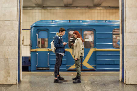 Full length shot of couple of teenagers using smartphones, totally absorbed in online life, ignoring each other while standing at the subway metro station