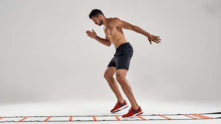 Never stop. Full length shot of young athletic man training on agility ladder drill isolated over grey background