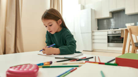 A cute little girl writing with a pencil while sitting at a table having multicolored pencils around the table 免版税图像