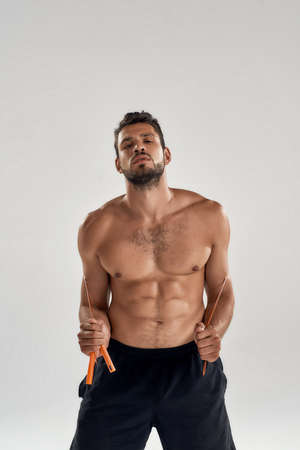 Cardio exercises. Young handsome muscular man with naked torso holding jumping rope on shoulders and looking at camera while standing isolated over grey background