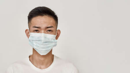 Portrait of young asian man in medical mask looking at camera isolated over white background. Health care, prevention, safety concept 免版税图像