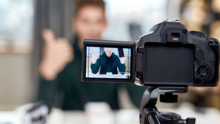 Close up of camera screen. Male technology blogger recording video blog or vlog review of new smartphone at home studio. Blogging, Work from Home concept 免版税图像