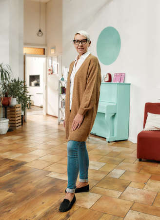 A fashionably dressed mature woman with her short hair cut and glasses on standing in a big creative workshop