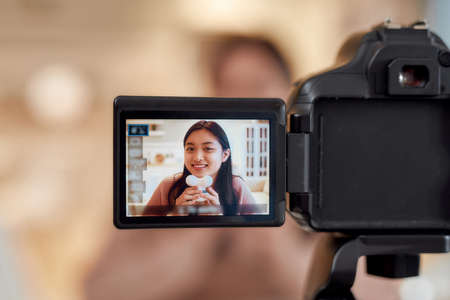 Close up of camera screen. Young female blogger massaging her chin with facial massager while recording a video for her beauty blog. Face lift, anti aging treatment concept