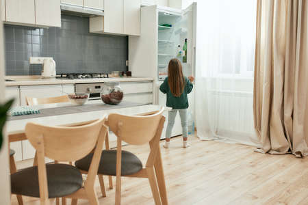 A little girl wearing green sweater and lightblue jeans is looking into a fridge in a bright kitchen while standing with her back to the camera 免版税图像