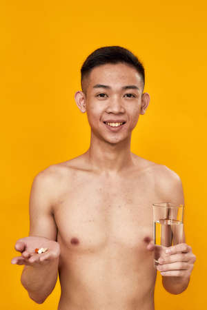Portrait of shirtless young asian man smiling at camera, holding pills and glass of water isolated over yellow background. Health care, treatment concept