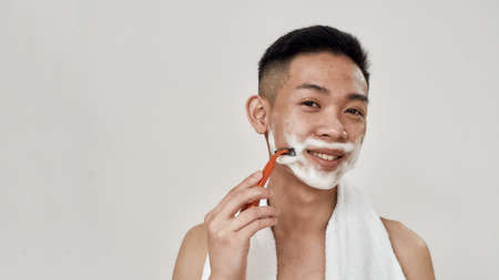 Portrait of young asian man with foam on his face holding a razor and shaving while smiling at camera isolated over white background. Beauty, skincare, morning routine