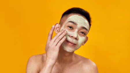Portrait of shirtless young asian man applying green mask on his face isolated over yellow background. Beauty, skincare routine concept