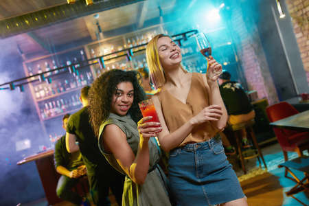 Attractive young women getting drunk, posing with cocktail in their hands. Friends celebrating, having fun in the bar