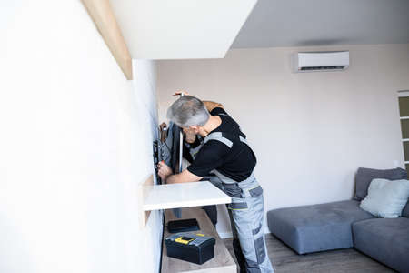Two professional technicians, workers in uniform installing, fixing mount tv, television on the wall indoors. Construction, maintenance and repair concept 免版税图像