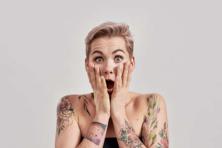 Amazement. Portrait of amazed tattooed woman with short hair looking amazed or shocked at camera with open mouth, touching face isolated over light background 免版税图像