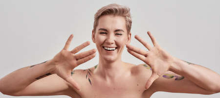 Hiya. Portrait of cheerful half naked tattooed woman with pierced nose and short hair waving at camera, raising two hands isolated over light background 免版税图像 - 157325103
