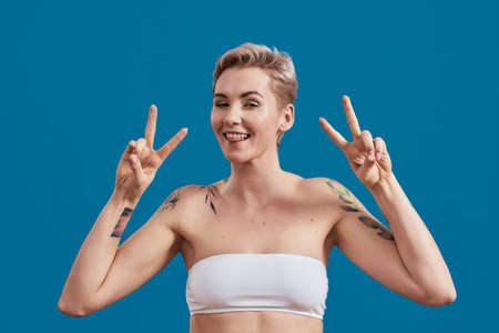 Portrait of a young attractive half naked tattooed woman with perfect skin looking happy, showing victory or peace sign with hands isolated over blue background 免版税图像 - 157325106
