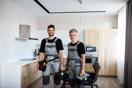 We make your life easier. Portrait of young and aged repairmen in uniform looking at camera with a smile, holding toolbox, ready for fixing kitchen hood. Repair service concept