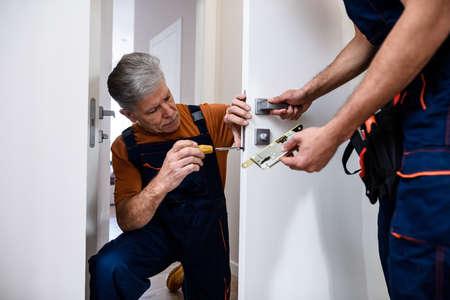 Aged locksmith, repairman, worker in uniform installing, working with house door lock using screwdriver while his colleague bringing him lock plate. Repair, door lock service concept