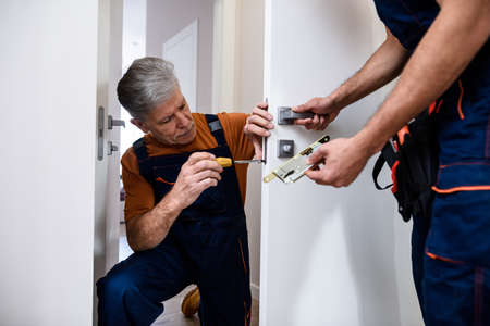 Aged locksmith, repairman, worker in uniform installing, working with house door lock using screwdriver while his colleague bringing him lock plate. Repair, door lock service concept