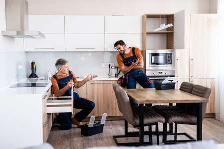 Full length shot of two handymen, workers in uniform talking while assembling kitchen cabinet using screwdriver indoors. Furniture repair and assembly concept