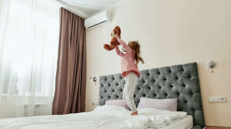 A small girl enjoys spending time holding a teddybear and staying on a huge bed barefoot