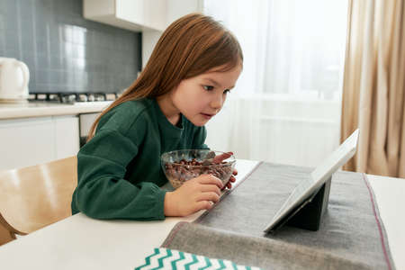 A small cute girl is looking closely in her tablet while eating a breakfast alone in a big light kitchen during distance eduation