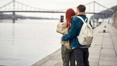 Two teenagers admiring the view, standing together near the riverside. Girl holding smartphone while taking photo of landscape
