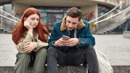 Two teenagers spending time together, sitting on the steps outdoors. Upset girl looking at her boyfriend while he is ignoring her, using his smartphone