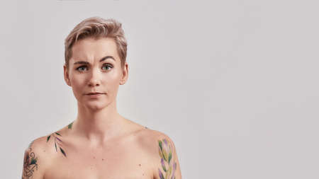 Portrait of half naked tattooed woman with perfect skin looking at camera, raising an eyebrow isolated over light background