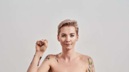 Stronger Together. Portrait of half naked tattooed woman with short hair looking at camera, holding hand with a clenched fist, fingers as if ready for challenge isolated over light background