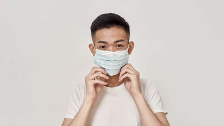Portrait of young asian man with problematic skin wearing medical mask isolated over white background. Health care, prevention, safety concept