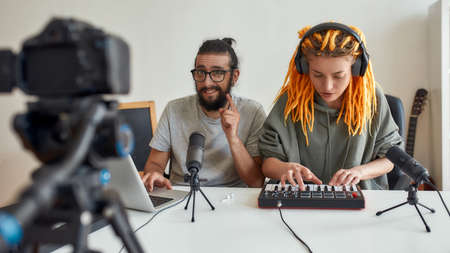 Man and woman making music using synthesizer, drum pad machine, laptop. Female and male blogger recording video blog or vlog at home