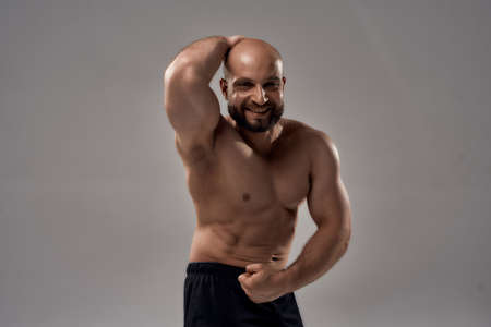 Muscular body. Strong athletic caucasian man bodybuilder showing his muscles, chest, biceps, abs and looking at camera while posing shirtless isolated over grey background