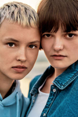 Close up portrait of two attractive young women with short hair looking at camera, Young lesbian couple spending time together