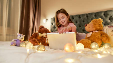 A cute little girl is sitting alone cross-legged on a big bed smiling while using a tablet showing to her teddybears