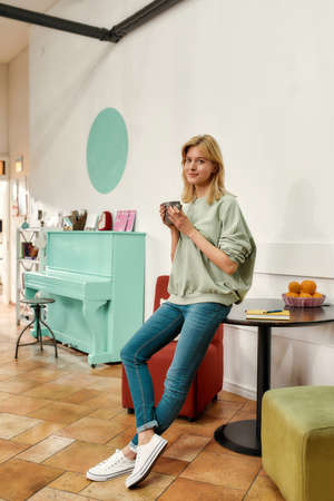 A cute blonde standing and drinking coffee wearing stylish clothes smiling looking into a camera