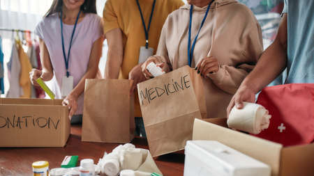 Cropped shot of group of volunteers packing medicine donation in paper bags and boxes for needy people, Small team working in charitable foundation