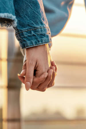 Close up of young lesbian couple holding each other hands, standing together outdoors 免版税图像
