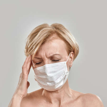 Close up portrait of middle aged woman wearing white medical mask, touching her temples, having headache, feeling stress isolated against grey background 免版税图像