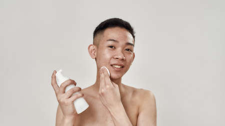 Portrait of shirtless young asian man with problematic skin cleaning his face with lotion using cotton pads, looking at camera isolated over white background 免版税图像